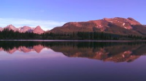 stock-footage-peaceful-lake-with-mountains-reflected-in-the-water