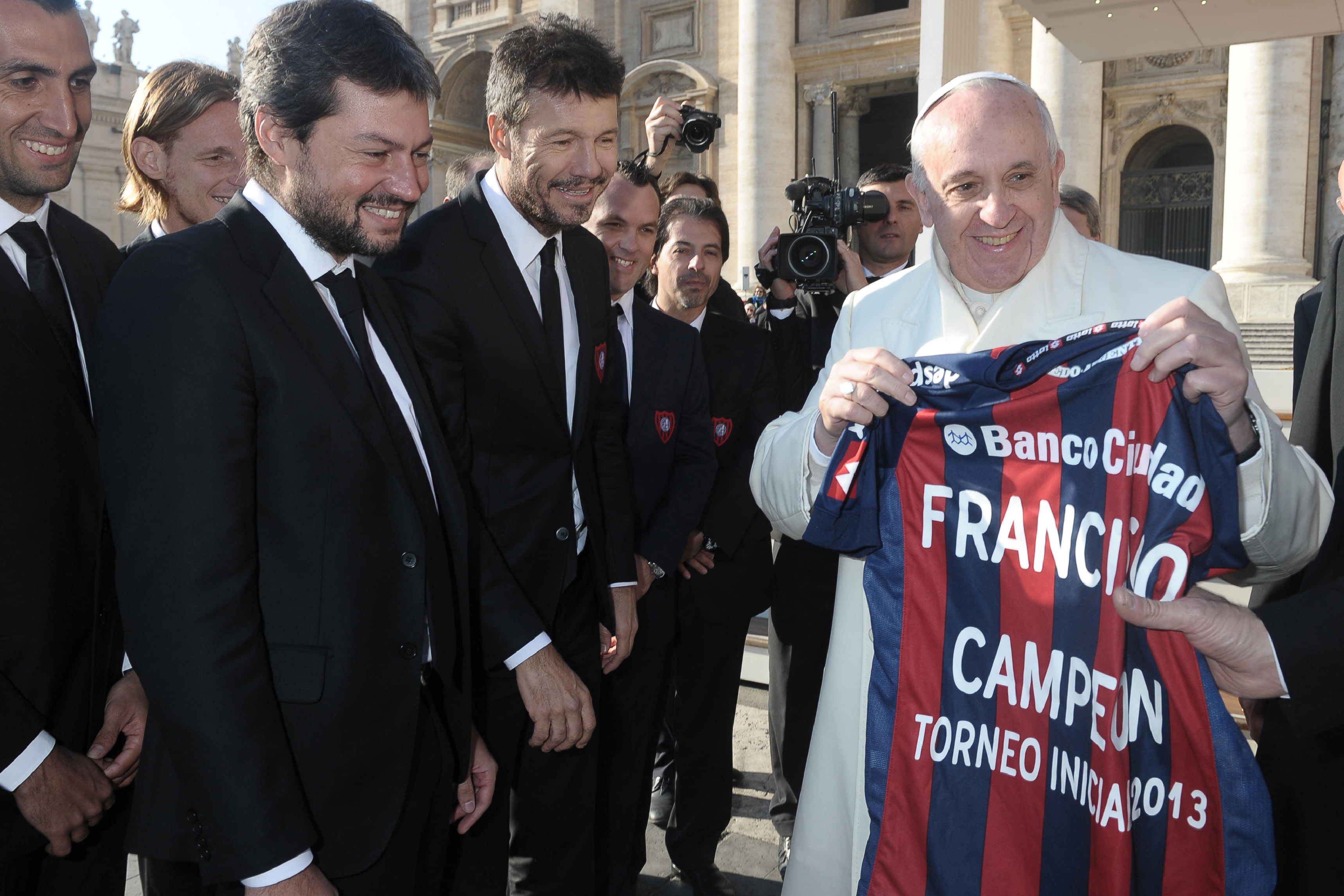 """In this picture provided by the Vatican newspaper L'Osservatore Romano, Pope Francis shows a jersey of San Lorenzo soccer team he was presented by team's President Matias Lammens, center, and deputy-president Marcelo Tinelli, second left, at the Vatican, Wednesday, Dec. 18, 2013. Pope Francis has celebrated his beloved San Lorenzo's victory in the Argentine soccer championship, hoisting up a replica of their trophy for all to see. A small group of team managers and players met with Francis on the steps of St. Peter's Basilica at the end of his Wednesday general audience. The group presented him with the replica of the trophy and a red and blue team jersey with """"Francisco Campeon"""" written on back. A clearly pleased Francis raised the trophy for all to see. San Lorenzo, of which then-Cardinal Jorge Mario Bergoglio was a registered fan, clinched the Argentine championship Sunday. (AP Photo/L'Osservatore Romano)"""