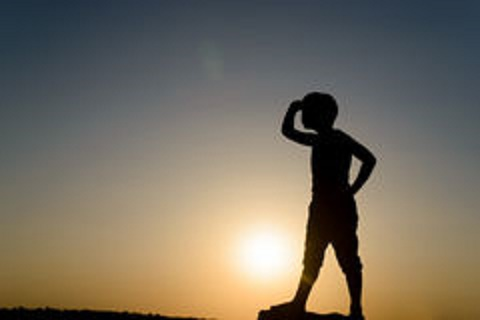 silhouette-young-boy-looking-distance-searching-hand-shielding-eyes-backlit-late-day-sun-copy-space-55435806